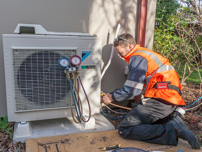 simon frost working on an outdoor heat pump unit